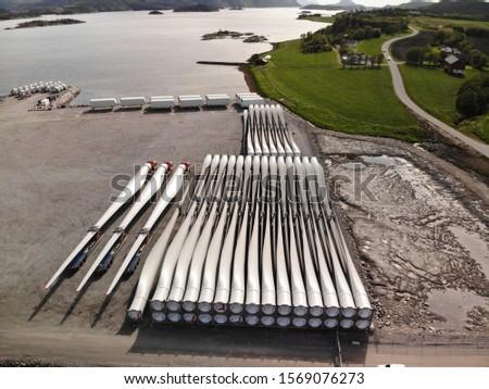 Wind turbine blades storage in Norway, fjord kai Royalty-Free Stock Photo #1569076273