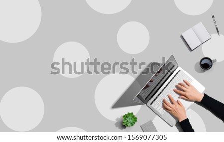 Person using a laptop computer from above #1569077305