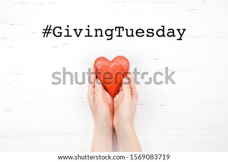 Giving Tuesday is a global day of charitable giving after Black Friday shopping day. Charity, give help, donations and support concept with text message sign and red wooden heart in woman hands #1569083719