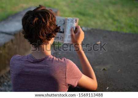 young boy reading a comic book in nature Royalty-Free Stock Photo #1569113488