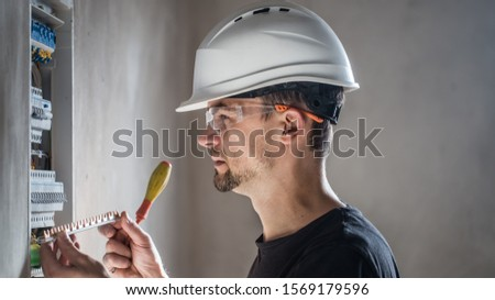 Man, an electrical technician working in a switchboard with fuses. Installation and connection of electrical equipment. Professional with tools in hand. concept of complex work, space for text. #1569179596