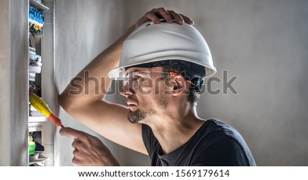 Man, an electrical technician working in a switchboard with fuses. Installation and connection of electrical equipment. Professional with tools in hand. concept of complex work, space for text. #1569179614