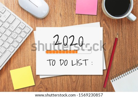 New Year Resolution Goal List 2020 - Business office desk with notebook written in handwriting about plan listing of new year goals and resolutions setting. Change and determination concept. #1569230857