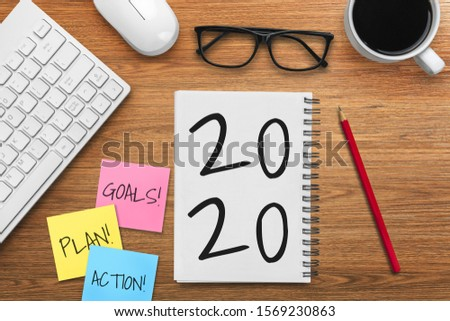 New Year Resolution Goal List 2020 - Business office desk with notebook written in handwriting about plan listing of new year goals and resolutions setting. Change and determination concept. #1569230863
