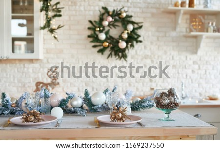 Interior light kitchen with christmas decor and tree. White kitchen in classic style. Christmas in the kitchen. Bright kitchen in white shades with Christmas. Christmas table setting.   #1569237550
