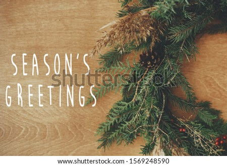 Season's greetings text sign on christmas rustic wreath flat lay. Creative rural wreath with fir branches, berries, pine cones, herbs on wooden table. Seasons greeting card #1569248590