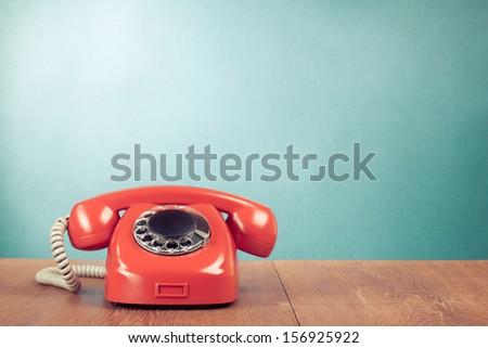 Retro red telephone on wood table near aquamarine wall background Royalty-Free Stock Photo #156925922