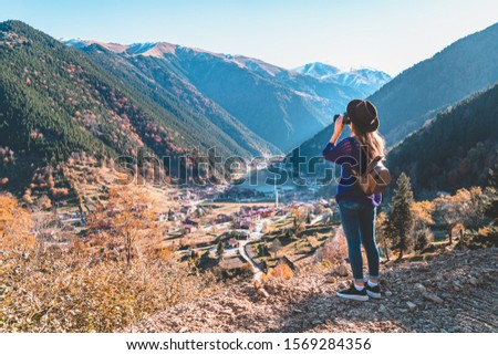 Stylish trendy hipster woman traveler photographer in a felt hat with brown backpack taking pictures of the mountains and uzungol lake in Trabzon during Turkey travel