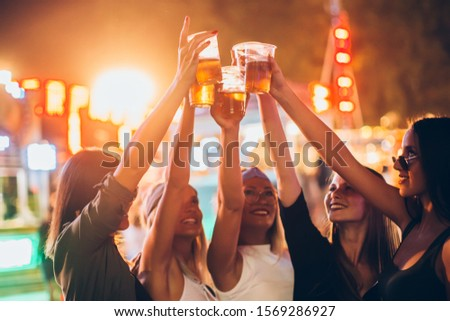 Group of female friends cheering with beer in amusement park #1569286927