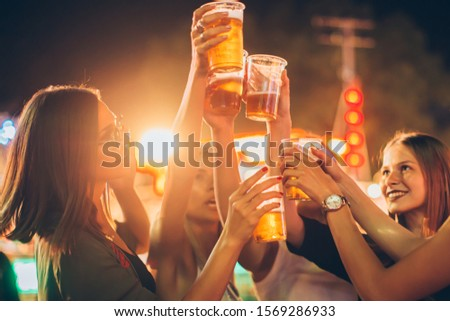 Close up of female friends cheering with beer in amusement park #1569286933