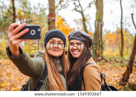 two pretty women taking selfie picture on phone outdoors at autumn city park