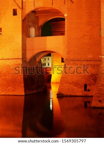 Ferrara, Italy. Este castle by night, detail. Bridge and moat with water. #1569305797