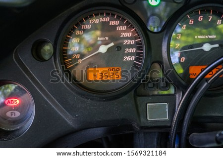 Speedometer of motorcycle on a open road from rider point of view. Motorcycle speedometer Royalty-Free Stock Photo #1569321184