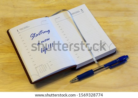 """The diary is open on the first of January page. On the page that says: """"Starting a new life!!!"""". #1569328774"""