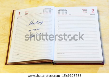 """The diary is open on the first of January page. On the page that says: """"Starting a new life!!!"""". #1569328786"""