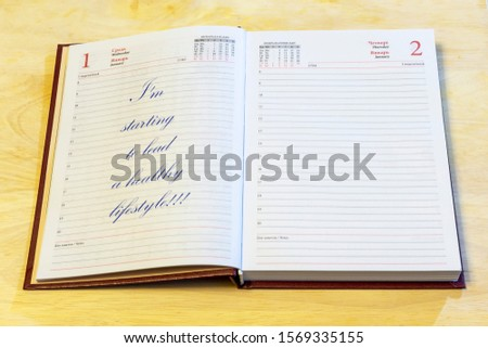 """The diary is on the table. The diary is open on the first of January page. The page reads: """"I'm starting to lead a healthy lifestyle!!!"""". #1569335155"""