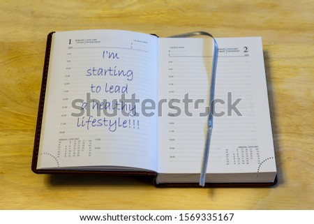 """The diary is on the table. The diary is open on the first of January page. The page reads: """"I'm starting to lead a healthy lifestyle!!!"""". #1569335167"""