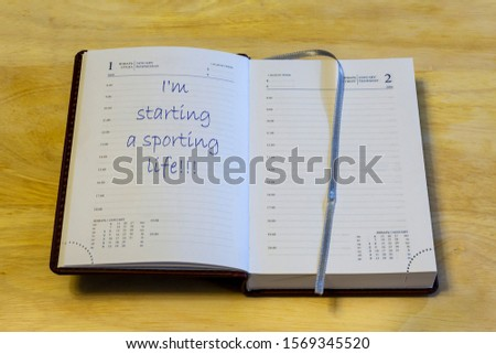 """The diary is on the table. The diary is open on the first of January page. The page reads: """"I'm starting a sporting life!!!"""". #1569345520"""