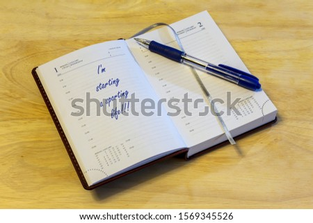"""The diary is on the table. The diary is open on the first of January page. The page reads: """"I'm starting a sporting life!!!"""". #1569345526"""