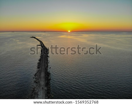 Aerial drone view of a long breakwater and sunset Royalty-Free Stock Photo #1569352768