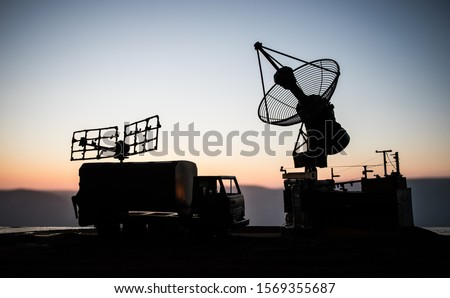 Creative artwork decoration. Silhouette of mobile air defence truck with radar antenna during sunset. Satellite dishes or radio antennas against evening sky. Selective focus Royalty-Free Stock Photo #1569355687