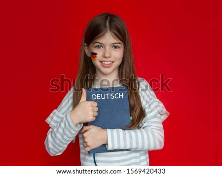 German language school concept. Portrait of a young girl with a painted German flag on her cheek. The book says German (in German) #1569420433