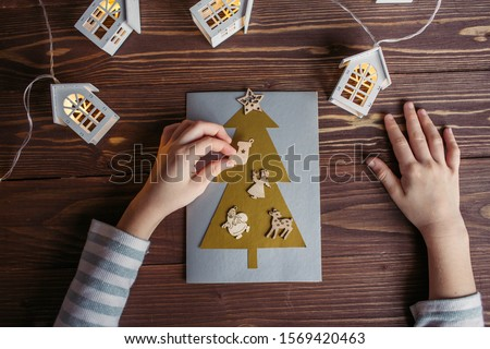 the child makes a New Year card for the winter holidays. DIY crafts and crafts for Christmas do-it-yourself concept #1569420463