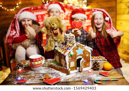 a group of small children play with toys on the background of Christmas decor and gingerbread house. #1569429403