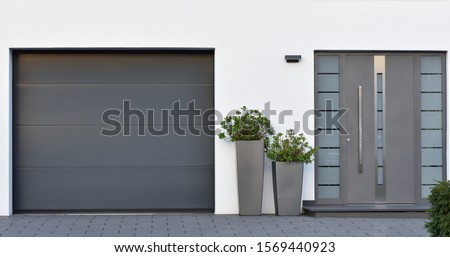 Modern gray garage, next to the Scandinavian-style house. Private garage with automatic door in a European city in Germany #1569440923