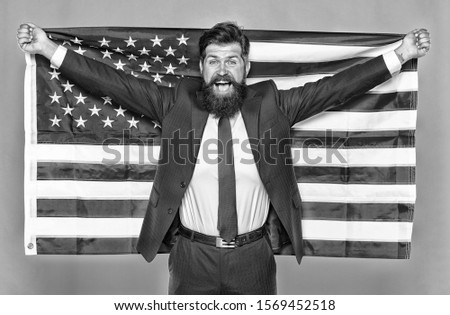 The patriotic spirit. Patriotic man holding american flag on independence day. Bearded businessman being patriotic for usa. The average american is nothing if not patriotic. #1569452518