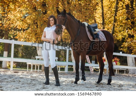 Young woman posing with wild horse in the field against the autumn forest. Love between horse and woman. #1569467890