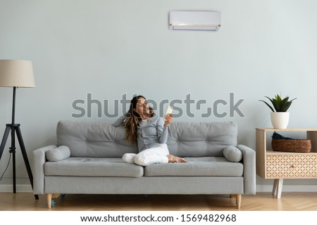 Woman spend time at home seated on sofa holding remote control manages degrees uses air conditioner enjoy air-conditioned contemporary flat, reduces heat or cold weather to comfortable temperature #1569482968