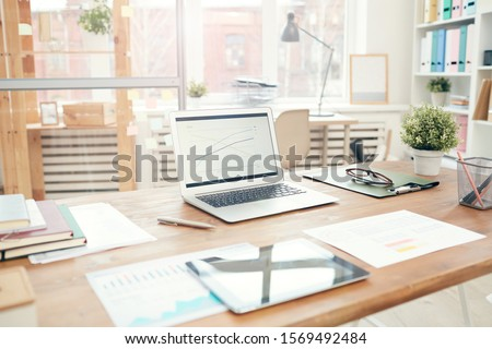 Background image of modern office interior with laptop on wooden table, workplace design concept, copy space Royalty-Free Stock Photo #1569492484