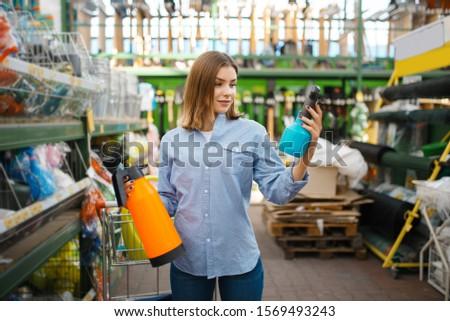 Customer choosing garden spray, shop for gardeners #1569493243