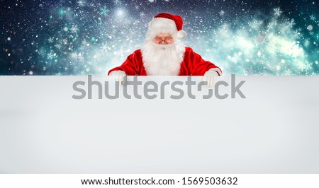 Happy Santa Claus holding Christmas blank advertisement banner background with copy space. Smiling Santa Claus pointing in white blank sign. Christmas theme, sales, space for your holiday text #1569503632
