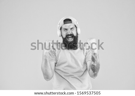He isnt nothing but a winner. Happy hipster shouting and making winner gesture on yellow background. Man winner listening to music in headphones. Excited winner or champion celebrating victory. #1569537505