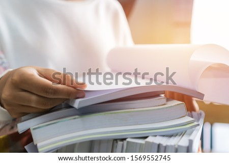 Businessman hands working in Stacks of paper files for searching information on work desk office, business report papers,piles of unfinished documents achieves with clips indoor,Business concept #1569552745