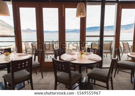 Penticton, British Columbia/Canada -  March 31, 2017: dining room with view of Okanagan Lake at the Hooded Merganser restaurant, part of the Penticton Lakeside Resort, a popular waterfront hotel #1569555967