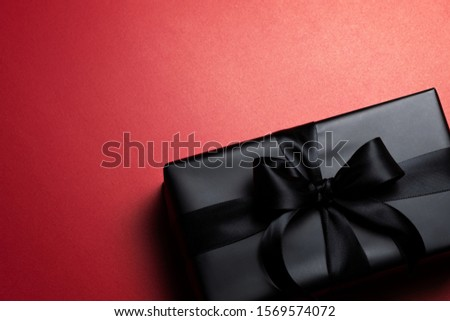 Top view of black christmas gift box with red and black ribbons isolated on red background. Shopping concept christmas day, valentin's day and black Friday sale composition. #1569574072