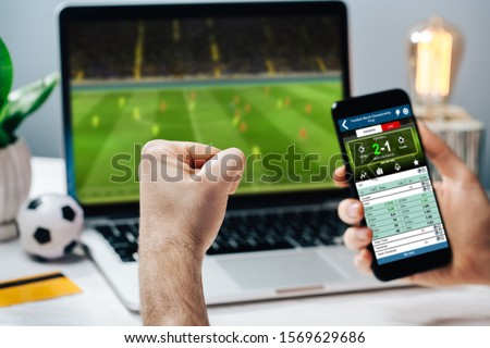 Lucky man celebrating money win. Male fan watching football play online broadcast on his laptop, cheering for his favorite team and making bets at bookmaker's website. #1569629686