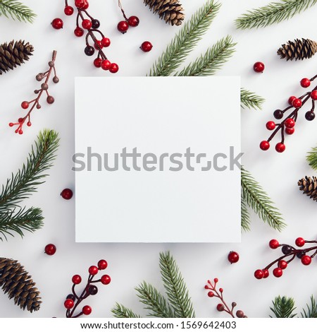 Christmas minimal concept - christmas composition made of evergreen tree branch, pinecone and red berries. Square composition. Flat lay, top view. White paper blank. Mockup template. Holiday frame. Royalty-Free Stock Photo #1569642403