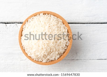 Uncooked white rice in bowl on rustic wooden table. Top view #1569647830