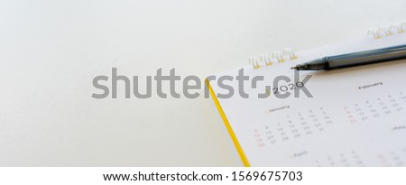 close up side view on  white calendar schedule background with pen to make appointment meeting or manage timetable each day for planning work in new year 2020 resolution concept