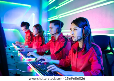 Team of asian teenage cyber sport gamers play in multiplayer PC video game on eSport tournament #1569686026