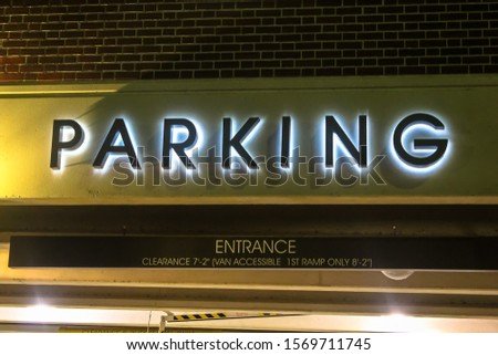 Illuminated Parking Sign letters on the outside of parking lot garage structure in city's downtown