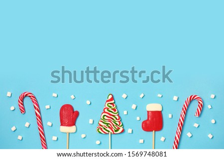 Christmas candies and mini marshmallows on blue background. candy shapes, candy cane. Flat lay, top view. Copy space #1569748081