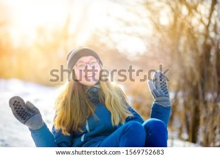 Cute girl sledding in a snowy winter park. Children have fun and have fun. Winter fun. #1569752683