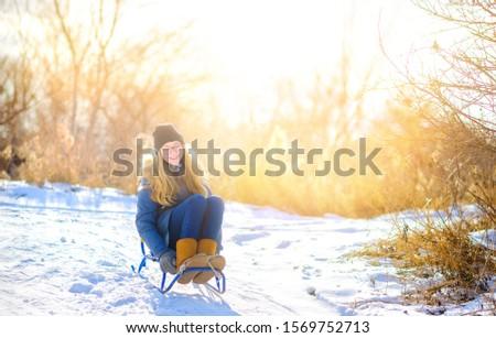 Cute girl sledding in a snowy winter park. Children have fun and have fun. Winter fun. #1569752713