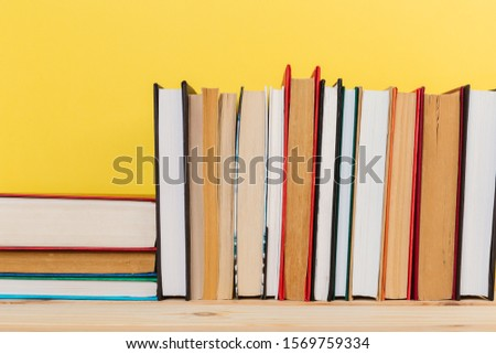 Simple Simple composition of many hardback books, unprocessed books on a wooden table and a yellow background. back to school. Copy space. Education. #1569759334