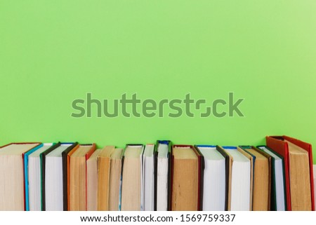 Simple Simple composition of many hardback books, unprocessed books on a wooden table and a green background. back to school. Copy space. Education. #1569759337